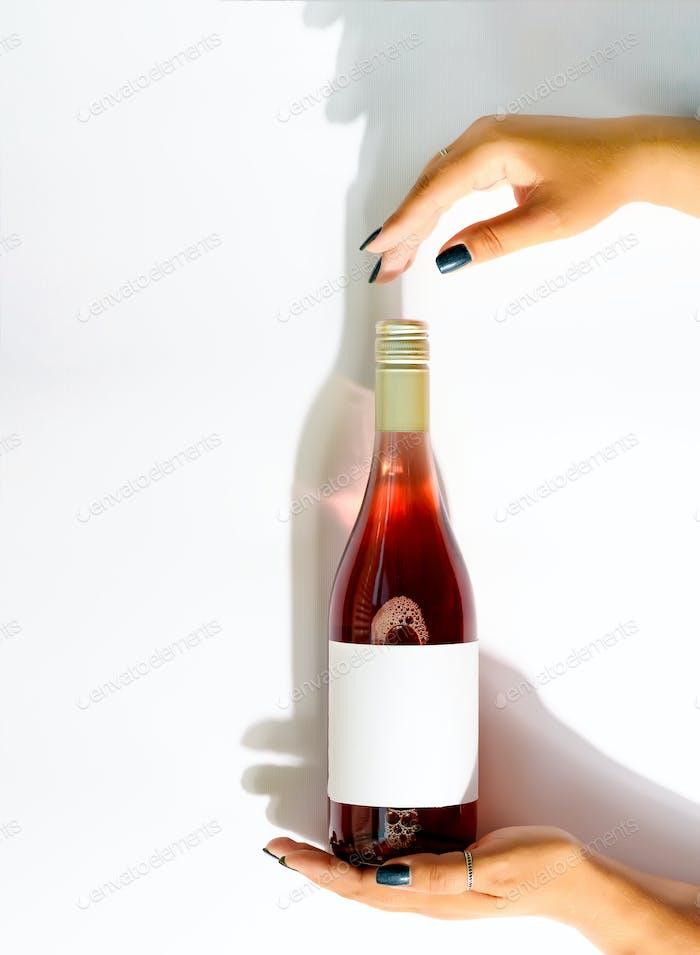 Eine Flasche Rosenwein in weiblichen Händen mit einem Mockup für ein Logo auf einem hellen Hintergrund in der Luft