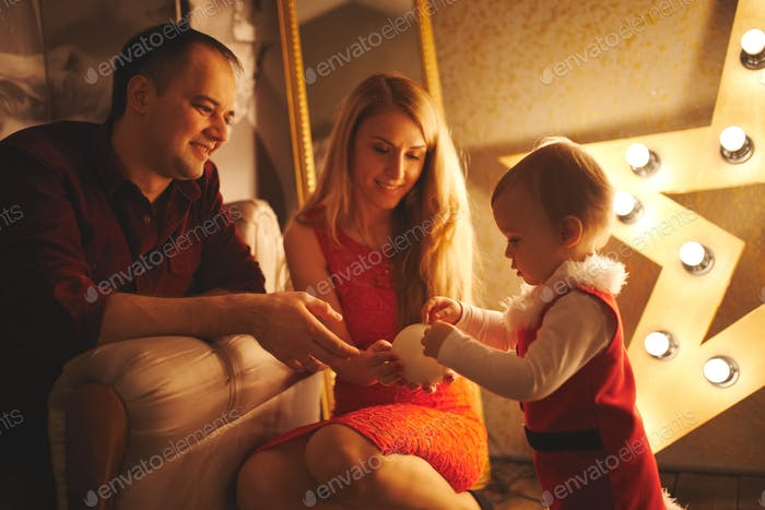 mother and father playing with daughter at home