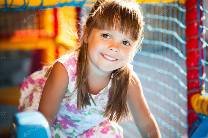 Small smiling girl in dress sitting in colorful soft decorative balls in playroom