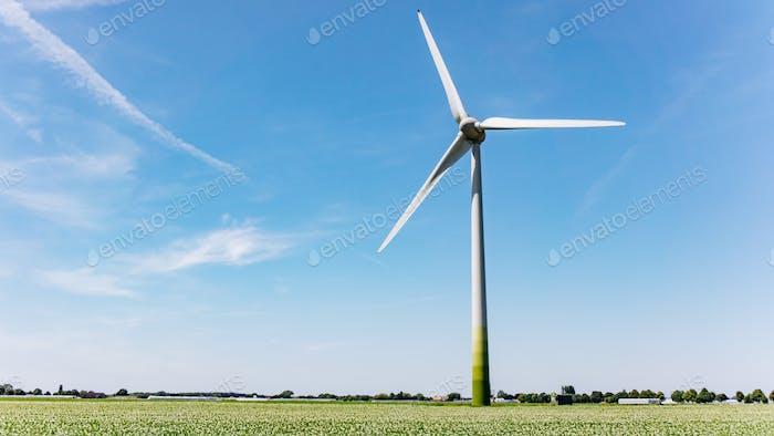 Windmill on a summer field. Mill on a green field. Beautiful landscape and mill.