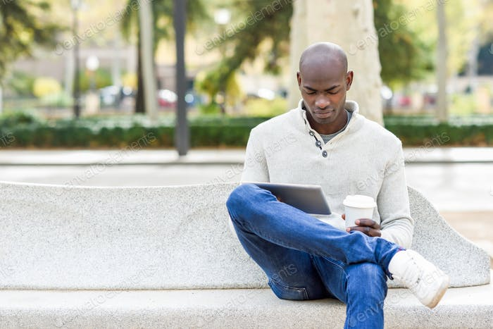 Black young man with tablet computer and take away coffee