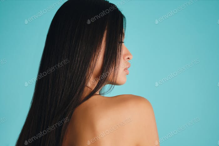 Side view of beautiful Asian girl with dark long hair sensually posing over colorful background