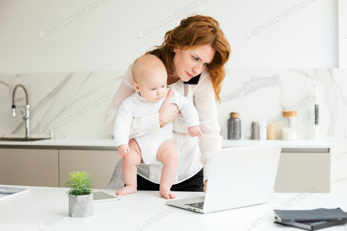 Business woman standing with her little baby in hand talking on her cellphone working on laptop
