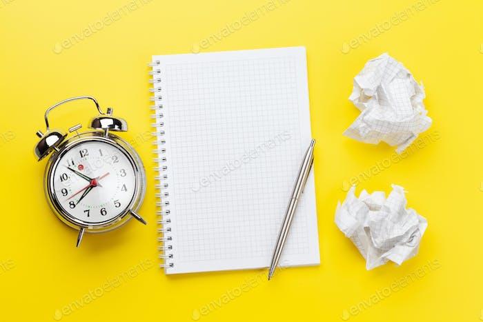 Büro-Schreibtisch mit Wecker und leerem Notizblock