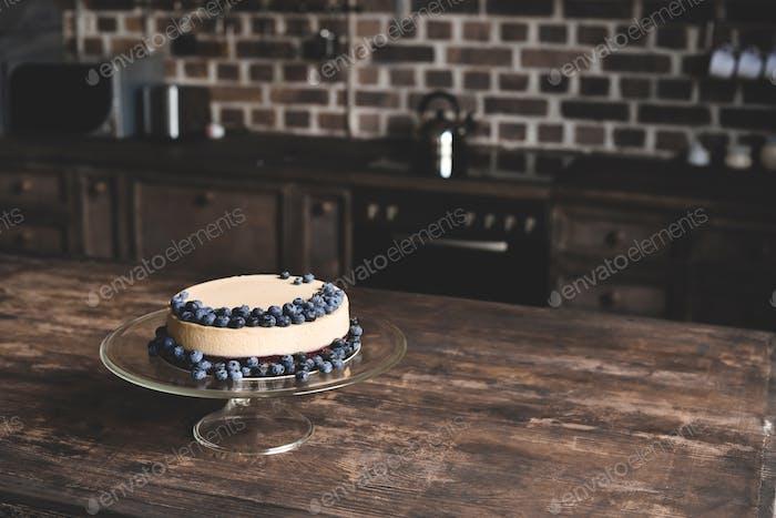 Käsekuchen mit Blaubeeren auf Glasständer auf Holztisch