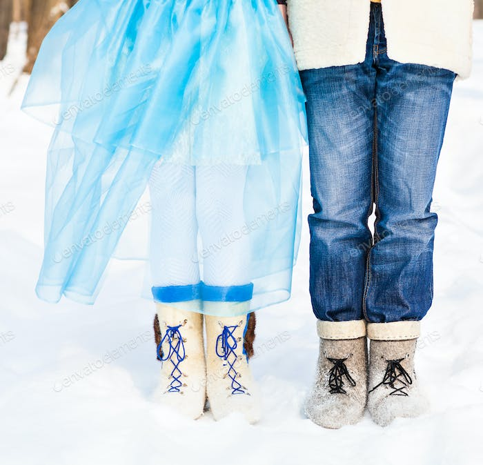 legs embracing couples standing on the snow snowy winter