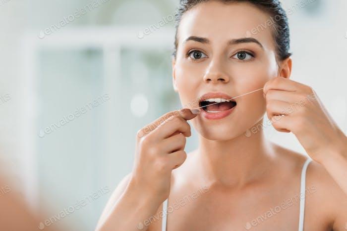 schöne junge Frau mit Zahnseide im Badezimmer