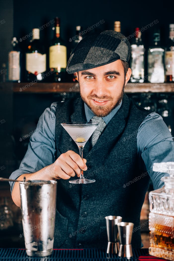 Handsome, vintage bartender preparing dry martini and serving to clients.
