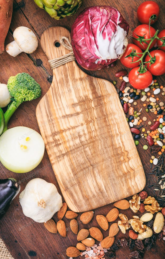Cutting board on wooden background. Empty wood cutting board surrounded of vegetables and nuts.