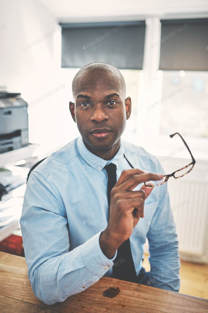 Confident and focused African businessman sitting in his home office