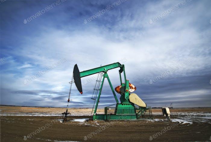 An oil pump jack at a drilling site for oil, an oil field in Saskatchewan.