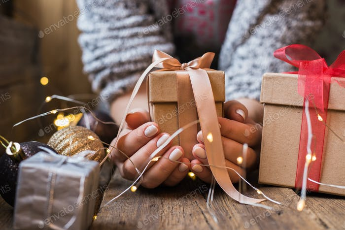 A woman holding a Christmas gift with a ribbon on a wooden table. Christmas presents and New Year