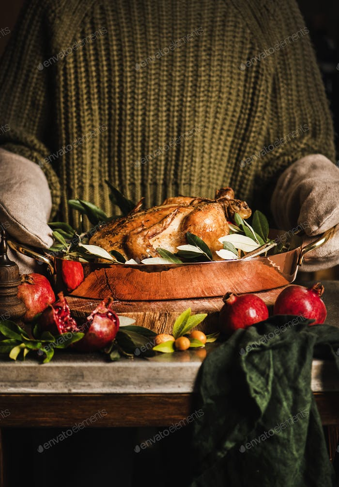 Woman holding roasting tin with whole roasted chicken for dinner