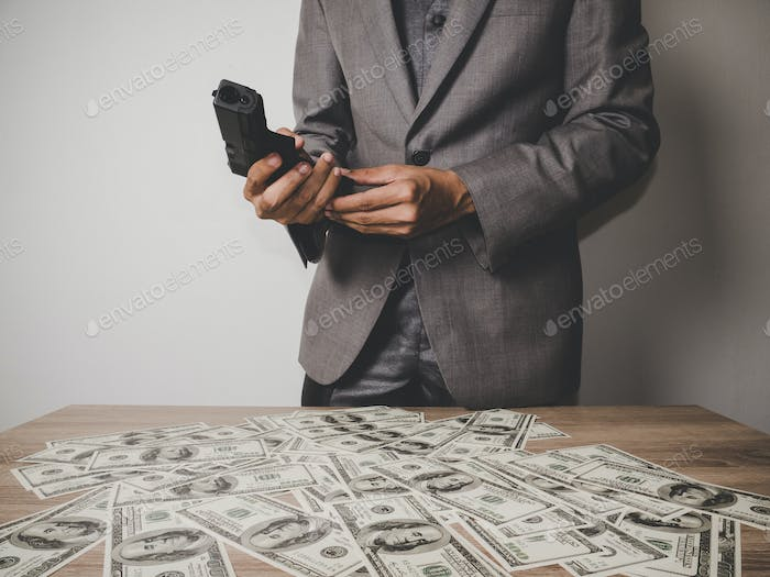 Gangster man hand holding a gun with dollar banknote