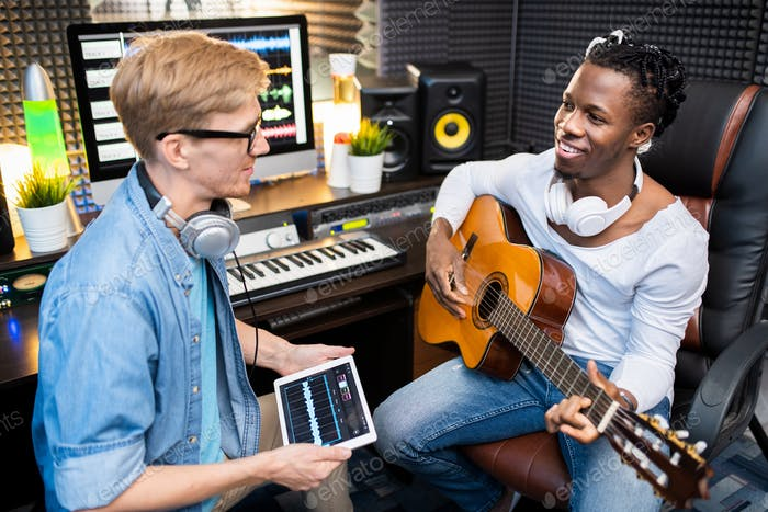 Young man with digital tablet talking to happy colleague with guitar