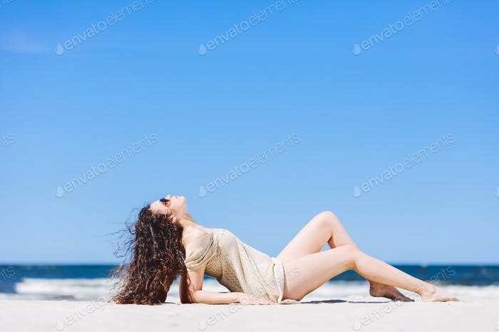 Young woman laying on the beach, sunbathing.