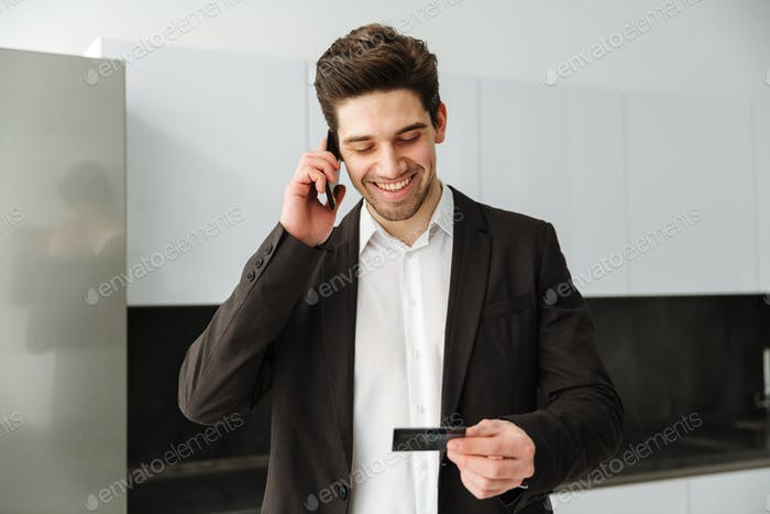 Happy young businessman talking by mobile phone holding credit card.