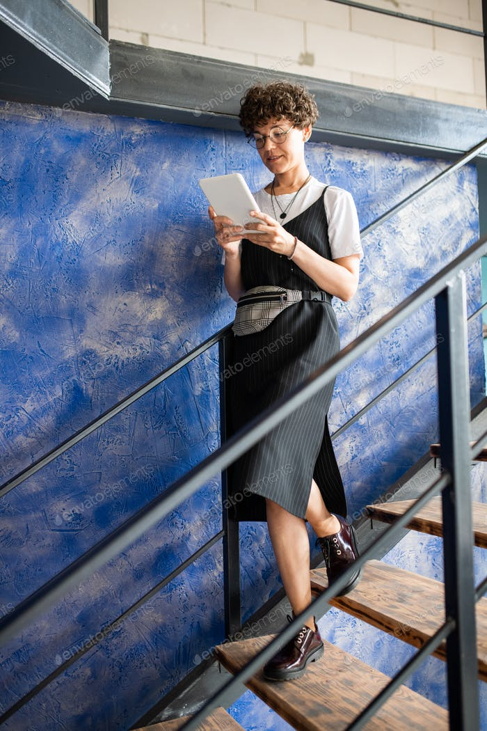 Pretty young businesswoman using mobile wireless gadget on staircase