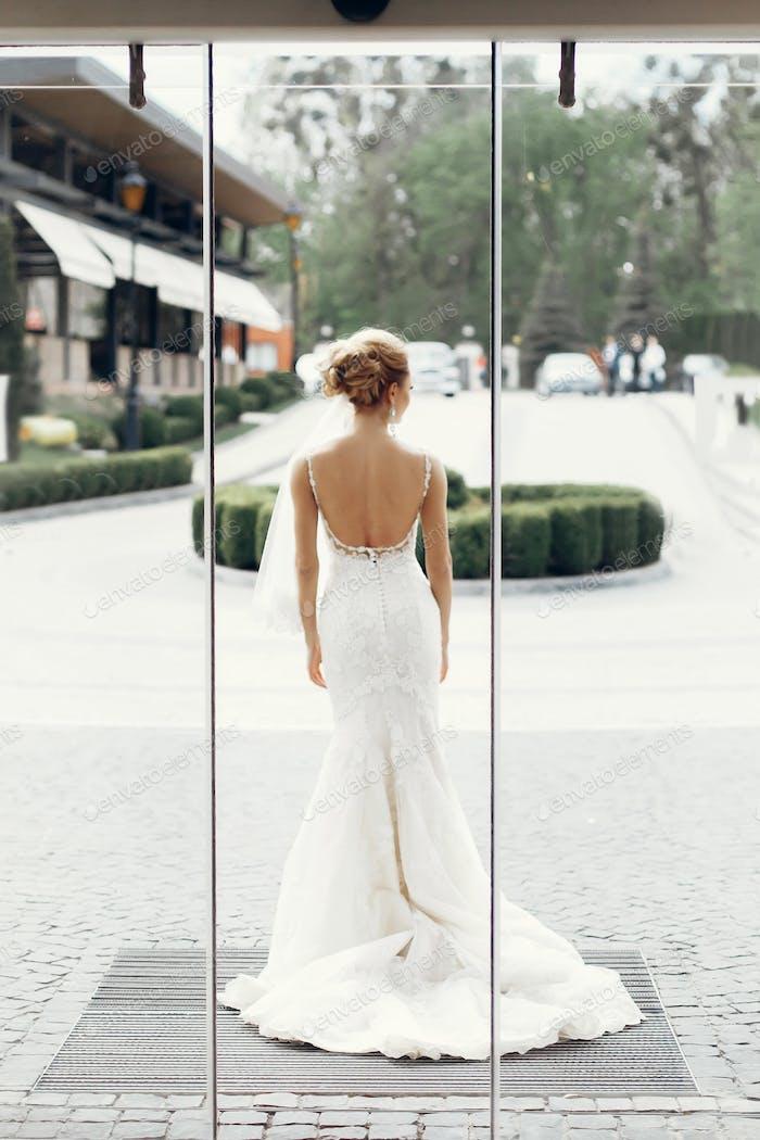 stylish bride posing at hotel glass door