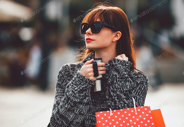 Woman walking on the street with coffee cup and shopping bags, city life concept