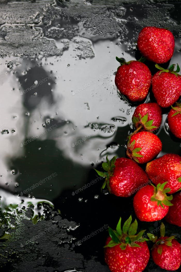 Whole strawberries on black background with water drops. Wet strawberries. Frame, copy space.