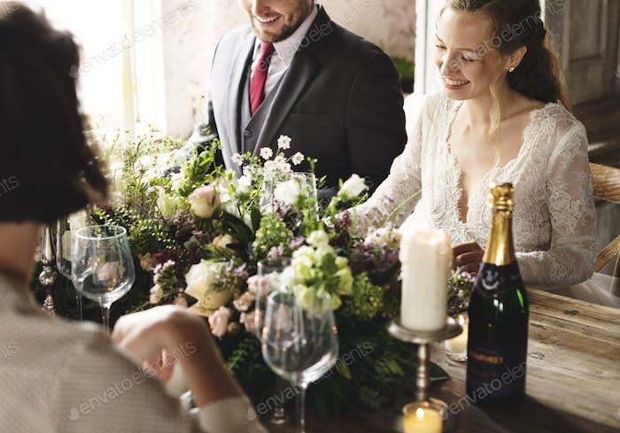 Braut und Bräutigam Essen mit Freunden bei Hochzeitsempfang