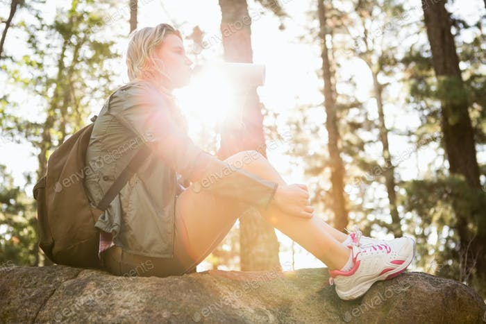 Pretty blonde hiker drinking and sitting on stone in the nature
