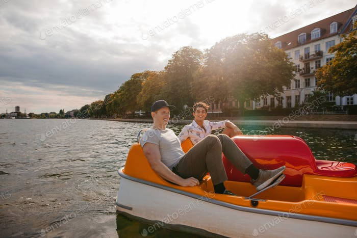 Teenage boys boating on the lake in city