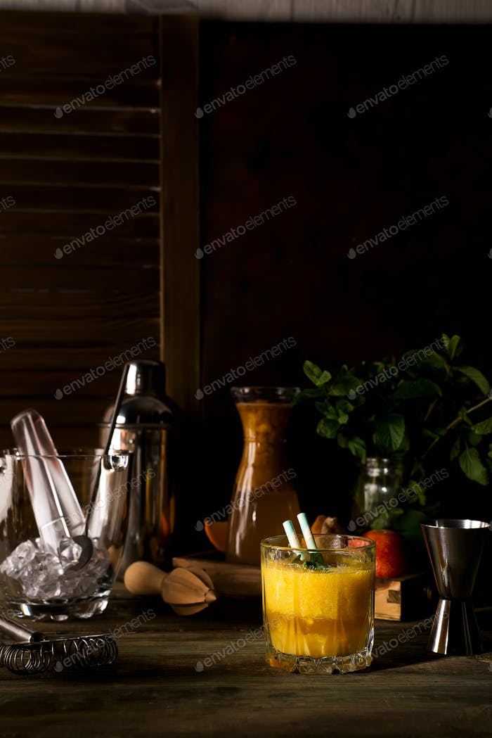 Smoothie cocktail of orange in a glass on dark wooden backgorund