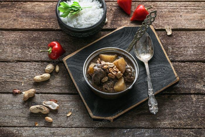 Thai-Beef Massaman Curry mit Reis, dunkler Hintergrund Kopie Raum