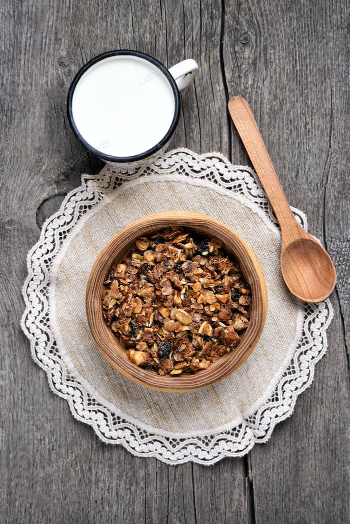 Chocolate granola in wooden bowl and milk
