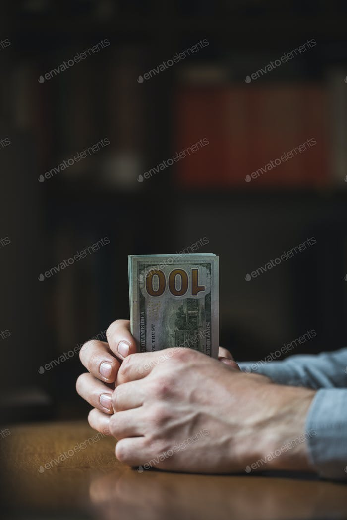Man's hand holding a dollar bill