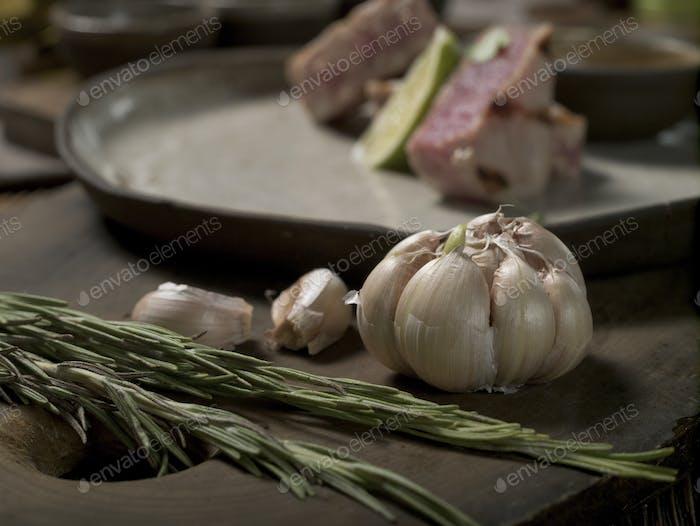 Rosmarin und Knoblauch auf einem Schneidebrett auf einem Hintergrund eines Tellers mit Thunfischsteak und Limette
