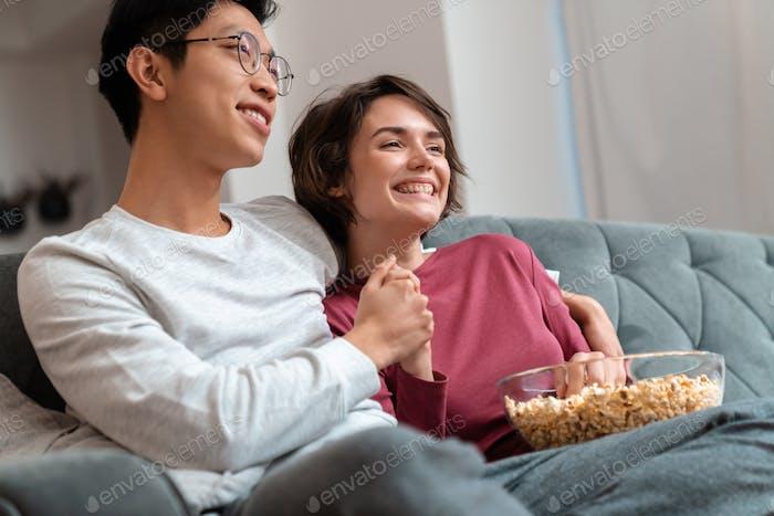 Foto des freudigen multinationalen Paares Popcorn essen und Film ansehen