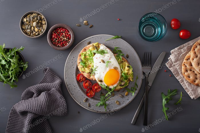 breakfast avocado sandwich with fried egg and tomato