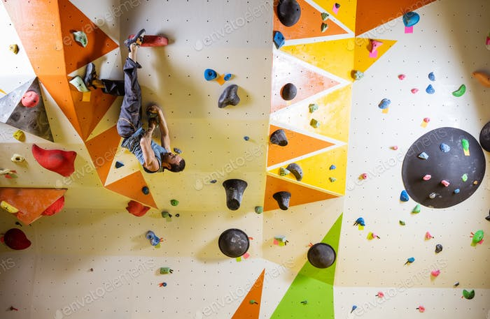 Young man climbing challenging bouldering route. In indoor climb