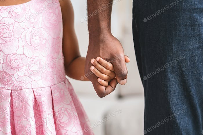 African american father and daughter holding hands