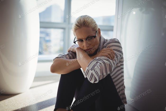 Sad executive sitting on floor