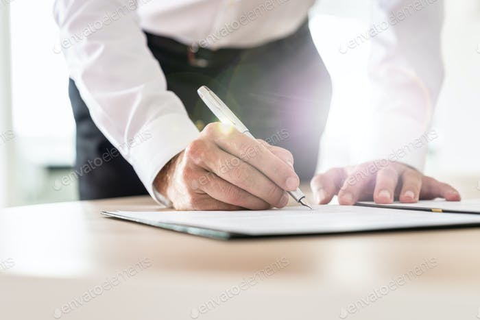 Unrecognizable businessman leaning in to sign a contract