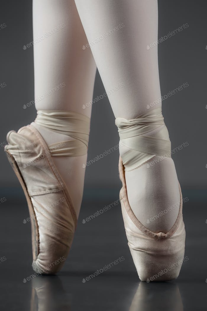 Ballerina standing en pointe in ballet slippers in the ballet studio
