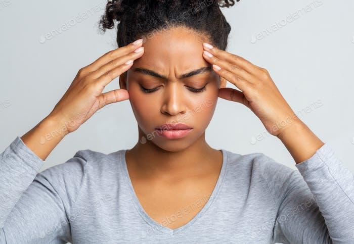 Sad black woman having headache, touching her temples