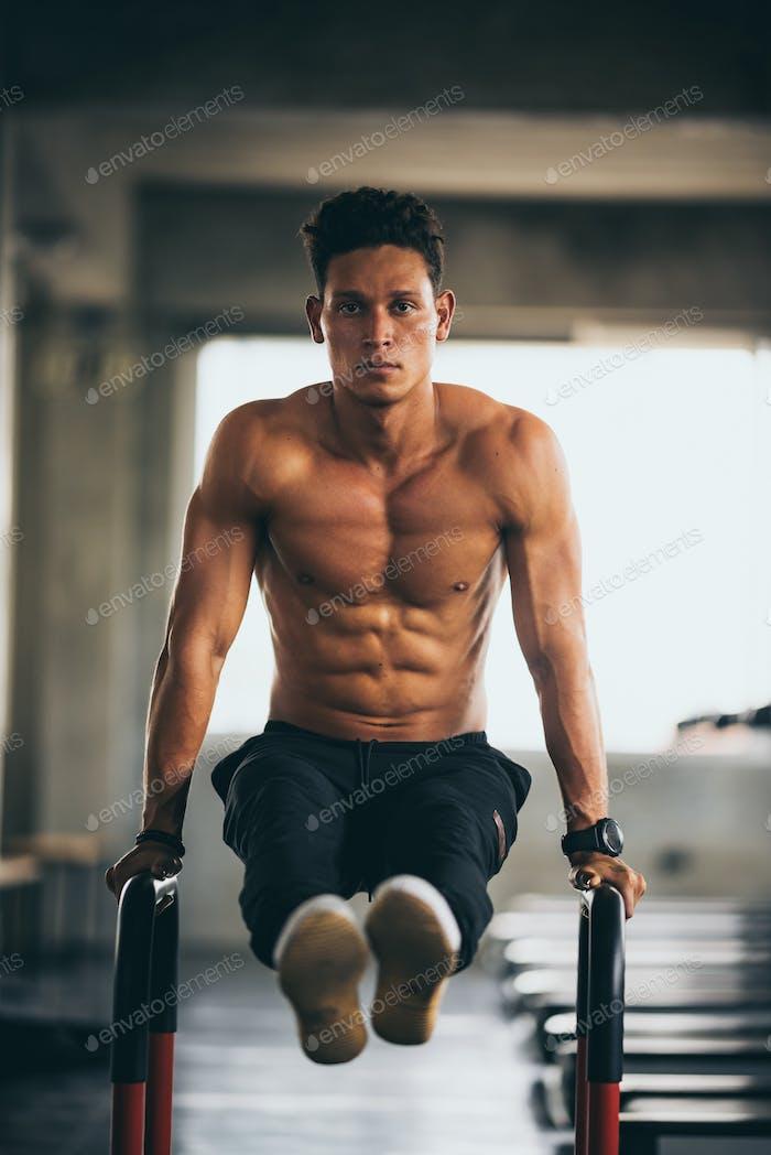junge Fitnessperson führt Übung mit Trainingsgerät im Fitnessstudio