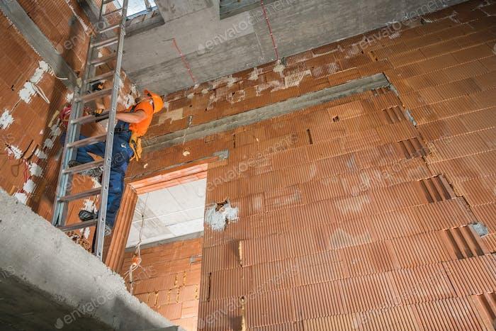 Trabajador de la construcción en una escalera dentro del edificio Comercial