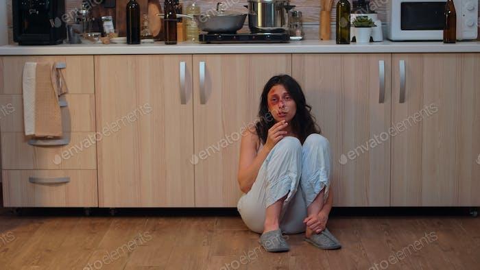 Mujer lesionada fumando sentado en el suelo