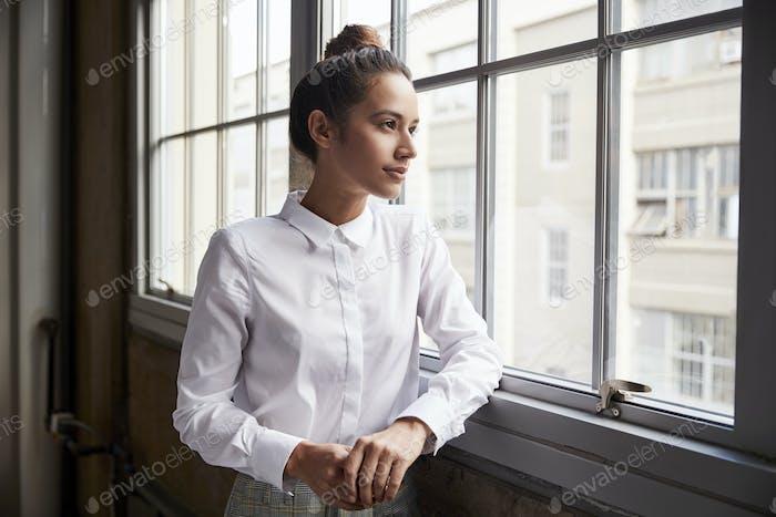 Junge Frau mit Haarknoten Blick aus dem Fenster, Taille nach oben