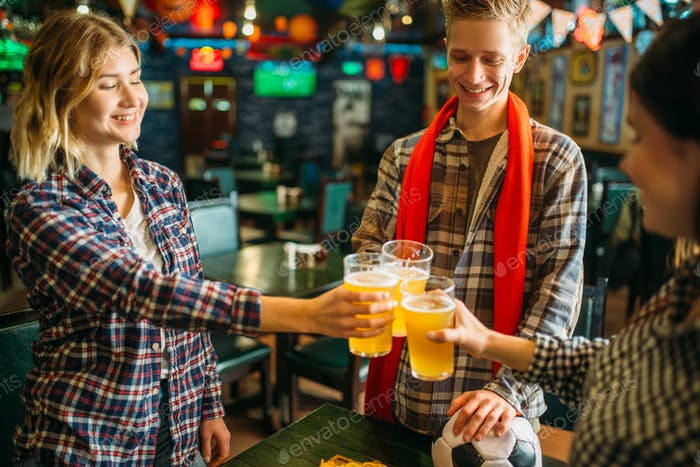 Football fans raise their glasses in sports bar