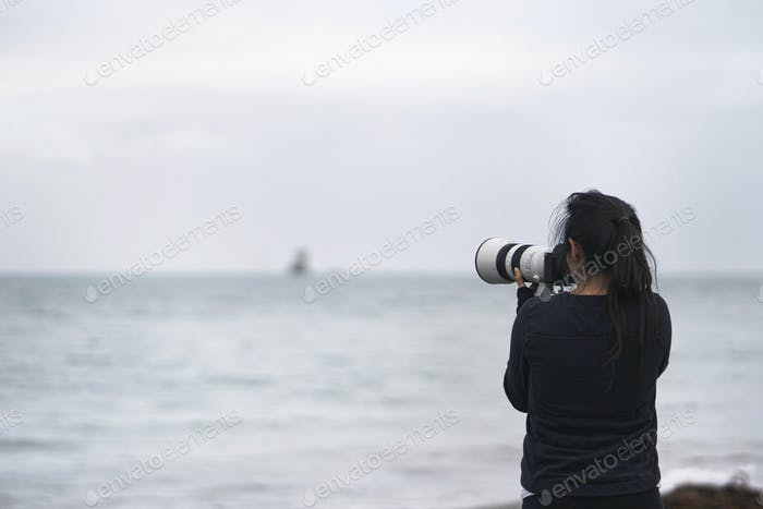 Female photographer capturing Seymour Tower, Channel Islands