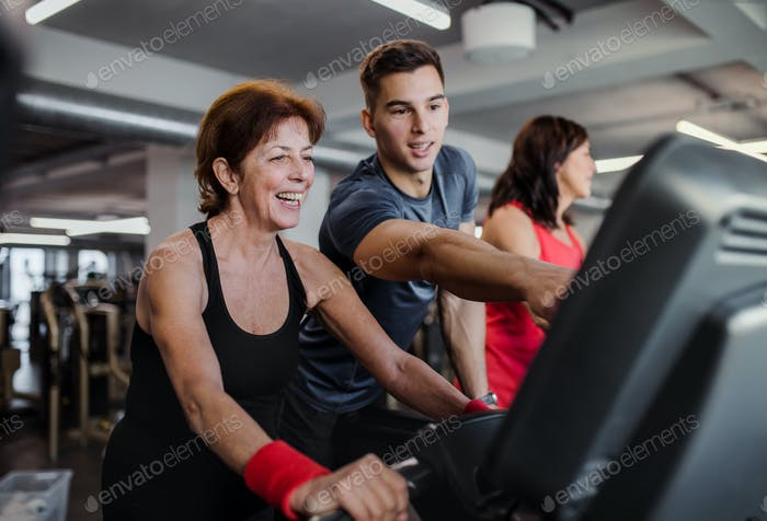 Two cheerful female seniors in gym with a young trainer doing cardio work out.