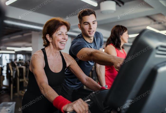 Zwei fröhliche Senioren im Fitnessstudio mit einem jungen Trainer beim Cardiotraining.