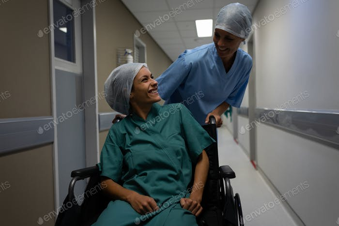 Female patient on wheelchair talking with female surgeon in the hospital corridor